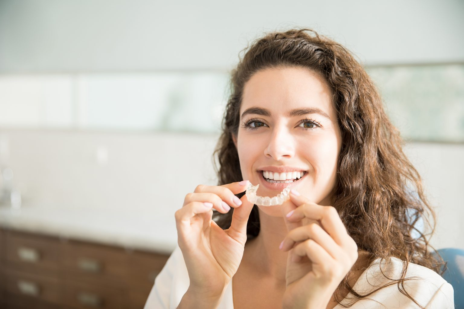 Beautiful Patient Holding Orthodontic Retainers In Dental Clinic